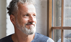 Aging man looking off, thinking about his financial wellness